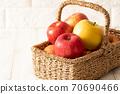 A full basket of freshly picked apples! White brick background 70690466