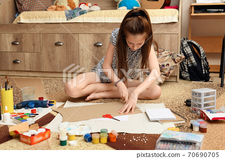 girl draws at home, artistic creation, makes creative artwork from paper, paints and brushes 70690705