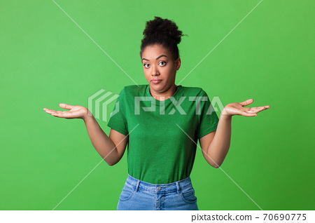 Confused puzzled black young lady shrugging at studio 70690775