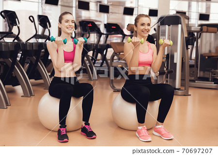 Girls doing exercise on fitness ball in the gym.  70697207