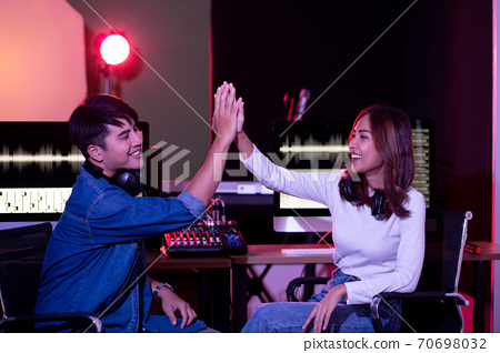 Portrait of asian young woman and man, artist singing into a microphone while recording a song in a studio 70698032