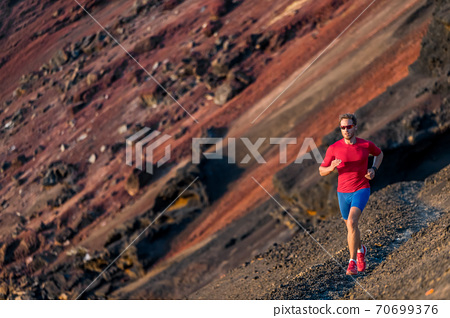 Man trail running in mountains. Runner on outdoor run. Fitness and health active lifestyle. 70699376