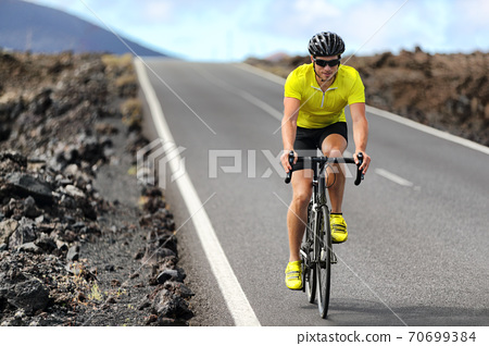 Road bike cyclist man cycling. Biking Sport fitness athlete biking on road bike. Active healthy sports lifestyle athlete cycling outside training for triathlon. 70699384