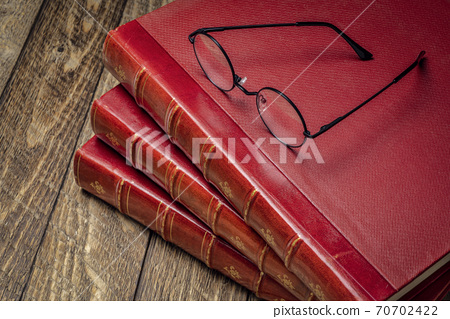 antique books and reading glasses 70702422