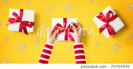 Person making Christmas gift boxes 70704940