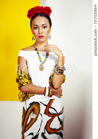 young pretty mexican woman smiling happy on yellow background, lifestyle people concept 70708964