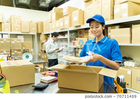 包裝在倉庫裡的年輕女子 70711489