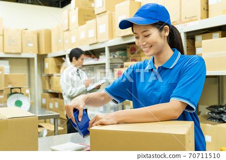 包裝在倉庫裡的年輕女子 70711510