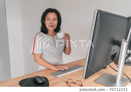 Mature Asian business woman working on standing desk at home office drinking coffee cup taking a break Businesswoman professional lady at work typing at computer people lifestyle. Lady in her 50s 70712252