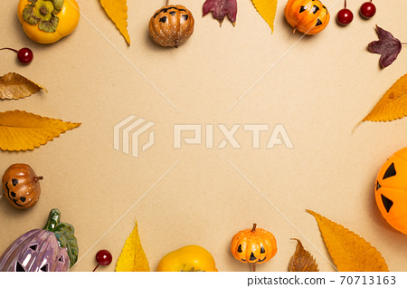 Halloween concept. Pumpkin and autumn leaves, sweet persimmon fruit on brown background. flat lay, top view, copy space 70713163