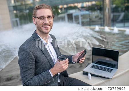 Male office worker sitting with coffee cup and laptop near fountain 70729995