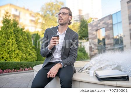 Male office worker enjoying coffee near fountain 70730001
