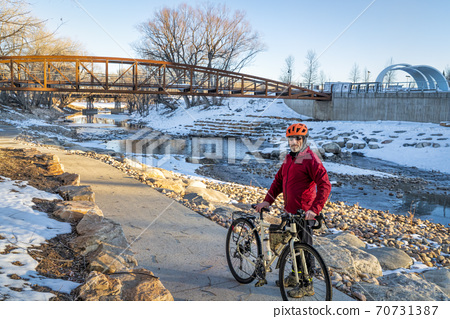 senior male cyclist is riding a bike in winter sunset scenery 70731387