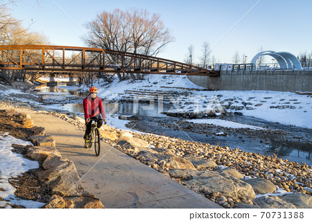 senior male cyclist is riding a bike in winter sunset scenery 70731388