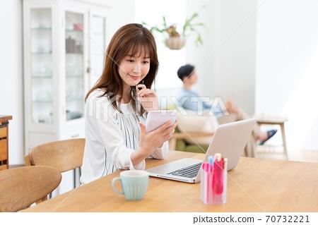 식탁에서 계산기를 미소 짓는 아내와 소파에서 휴식 남편 70732221