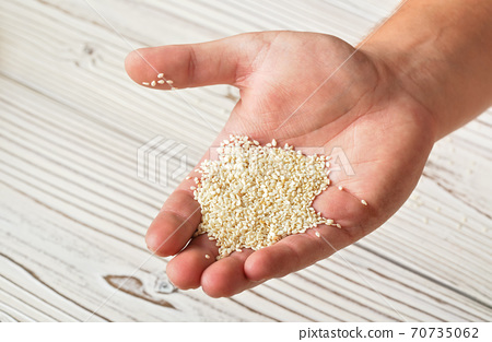 White sesame seeds in man hand, closeup detail, blurred boards table under 70735062