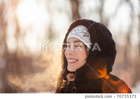 Winter cold Asian woman breathing in cold air with dewy mist clouds against sunlight in forest nature walk outdoor lifestyle. Happy people life style outside 70735373