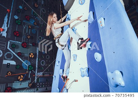 The girl stretches to the ledge on the walls  70735495