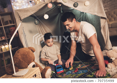 Father and son are playing with cars on road. 70735499
