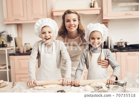 Mom hugs her children while smiling at the camera. 70735518