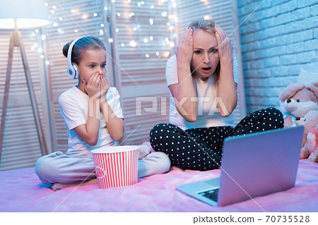Granddaughter and grandmother watch a movie. 70735528