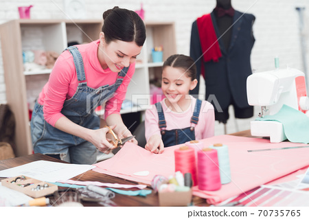 Mom shows the girl how to cut fabric. 70735765