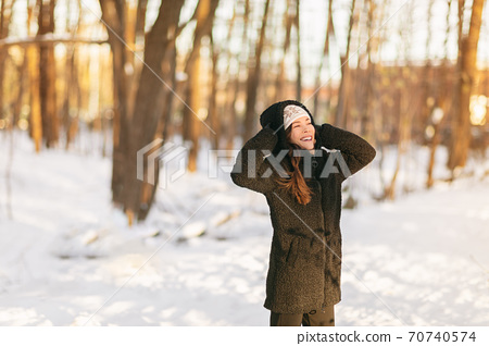 Winter snow fun happy girl walking outside in cold weather protecting ears holding wool hat over ears active outdoor lifestyle. Asian girl wearing teddy sherpa coat, gloves enjoying nature fresh air 70740574