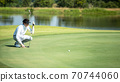 Golfer man playing golf aiming shot for putting ball on the hole with club on green course. 70744060