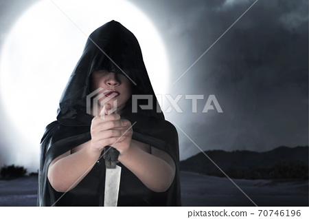 Asian witch woman with a cloak holding a knife standing 70746196