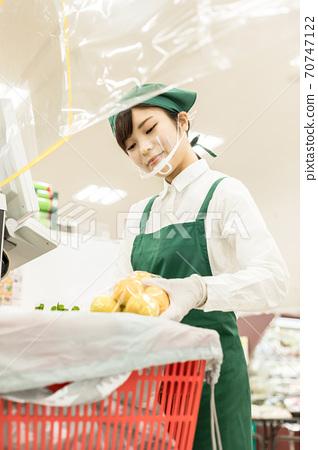 超市收銀機防護罩後面工作的人 70747122