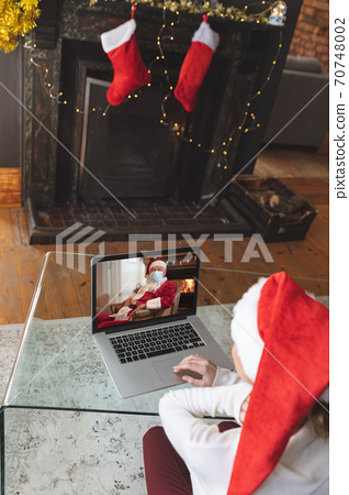 Woman in Santa hat having a video chat with Santa Claus in face mask on laptop at home 70748002