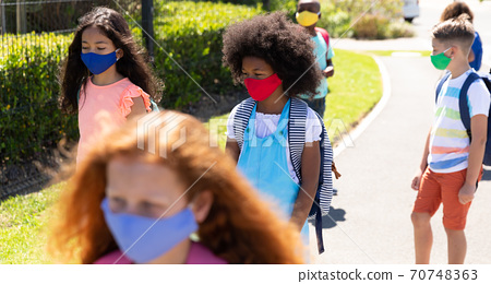 Group of kids wearing face masks walking on the road 70748363