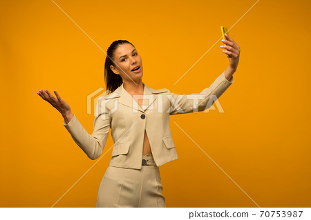 Young girl with facial skin problems posing with a smartphone on a yellow background 70753987