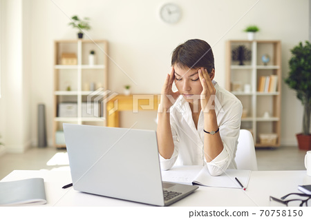 Tired woman with bad headache or blurry vision massaging temples sitting at desk with laptop 70758150
