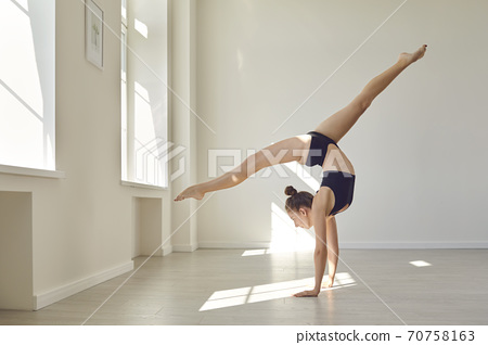 Girl gymnast practicing rhythmic gymnastics and body ballet in twine position on hands 70758163