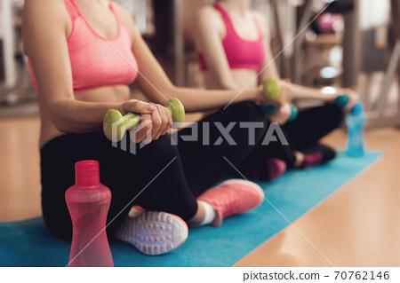 Two girls in sportswear with a bottle of water. 70762146