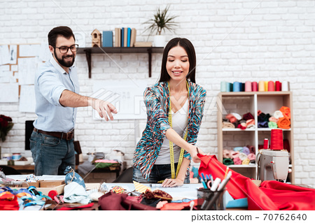 Two fashion designers hanfing over red cloth. 70762640