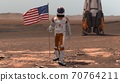 Astronaut walking on Mars with American flag. 70764211