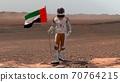 Astronaut walking on Mars with UAE flag. Exploring 70764215