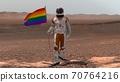 Astronaut walking on Mars with LGBT flag. 70764216