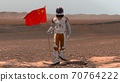 Astronaut walking on Mars with Chinese flag. 70764222