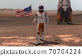 Astronaut walking on Mars with American flag. 70764224