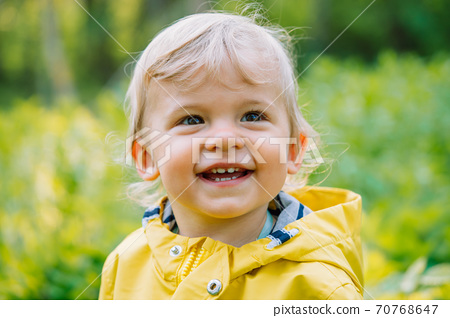 Portrait of cute baby boy in yellow raincoat. Child smiling. Love, care, attachment, family 70768647