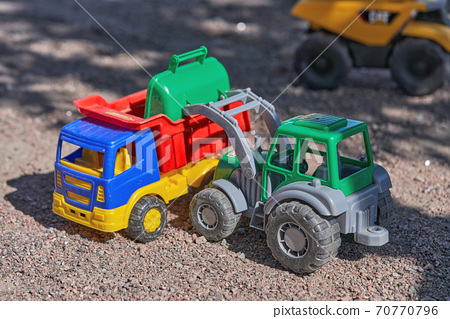 Toy plastic tractor loads dump truck with sand 70770796