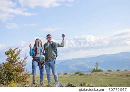 Happy travelers couple conquered top of mountain, raises hands up 70773047