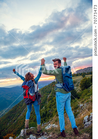 Couple on Top of a Mountain Shaking Raised Hands 70773473