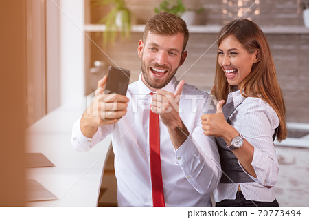 beautiful business workers working together using laptop at the office doing happy thumbs up gesture with hand. 70773494