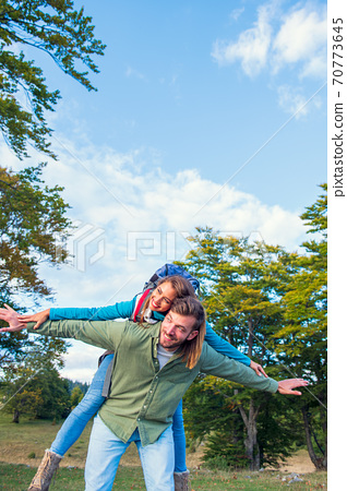 happy couple with backpacks traveling in highlands. Boyfriend carrying his girlfriend on piggyback. 70773645