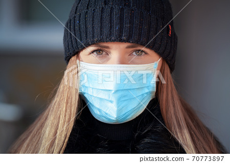 Young woman wearing blue disposable virus face mouth nose mask and warm beanie hat, closeup portrait, blurred background. Coronavirus covid-19 outbreak prevention illustration 70773897