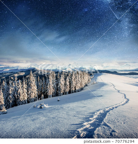 starry sky in winter snowy night. fantastic milky way in the New Year's Eve. In anticipation of the holiday. Dramatic scene. Carpathian. Ukraine 70776294